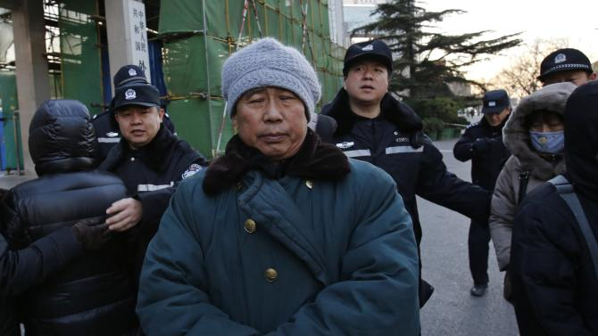Zhang Yongli, whose daughter Zhang Qi was onboard Malaysian Airlines Flight MH370 which disappeared, closes his eyes as police stop him from entering the Foreign Ministry's headquarters in Beijing