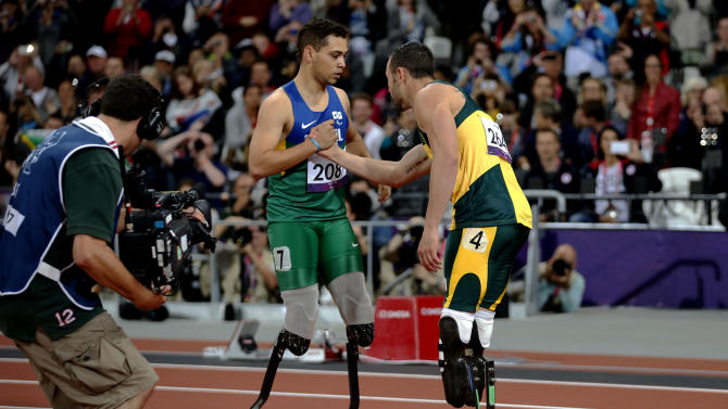 Gold medal winner Brazil's Alan Fonteles Cardoso Oliveira, left, embraces silver medalist south Africa's Oscar Pistorius after they ran the men's 200m T44 category final during the athletics competition at the 2012 Paralympics, Sunday, Sept. 2, 2012, in London.  (AP Photo/Matt Dunham)