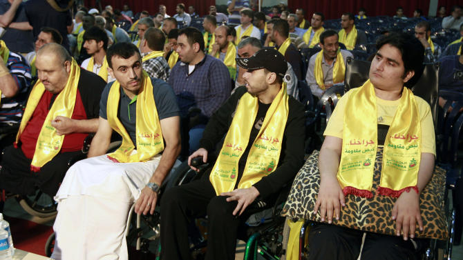 "Injured Hezbollah fighters listen to a speech by Hezbollah leader Sheik Hassan Nasrallah on a screen via a video link during a rally to mark ""wounded resistant's day,"" in the southern suburb of Beirut, Lebanon, Friday, June 14, 2013. Nasrallah said his group will continue to fight in Syria ""wherever needed,"" and said he has made a ""calculated"" decision to defend Syria and is ready to bear all consequences. (AP Photo/Bilal Hussein)"
