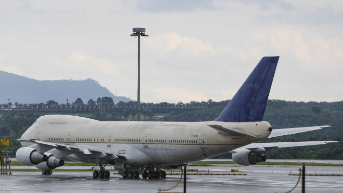 One of the three abandoned planes with tail number, TF-ARM, is seen taxied on the tarmac of Kuala Lumpur International Airport in Sepang, Malaysia, Wednesday, Dec. 9, 2015. Malaysia's airport operator has an unusual dilemma after three large Boeing planes were left abandoned at the country's main airport for more than a year.(AP Photo/Joshua Paul)