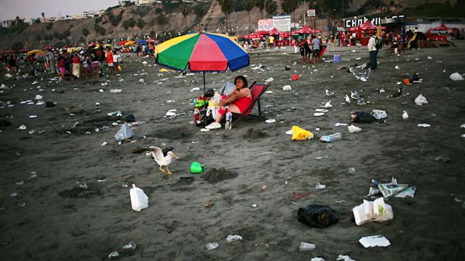 In this Jan. 20, 2013 photo, a woman lounges on a beach chair on a littered Agua Dulce beach in Lima, Peru. While Lima's elite spends its summer weekends in gate beach enclaves south of the Peruvian capital, the working class jams by the thousands on a single municipal beach of grayish-brown sands and gentle waves. On some weekends during the Southern Hemisphere summer, which runs from December until March, as many as 40,000 people a day visit the half-mile-long (kilometer-long) strip of Agua Dulce. Beachgoers arrive in groups of 20-30, hauling enormous pots of fragrant chicken and rice. (AP Photo/Rodrigo Abd)