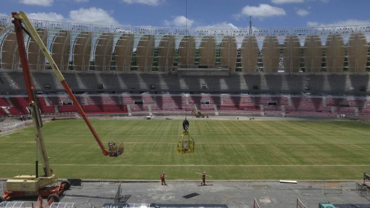 Workmen stand next to the pitch inside the Estadio Beira-Rio stadium as work continues in preparation for the 2014 World Cup soccer championship in Porto Alegre