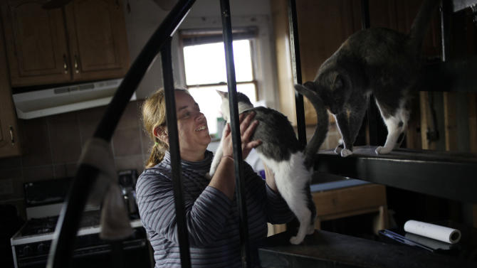 In this Monday, Dec. 3, 2012 photo, Rachael Alhadad greets some of her cats at her family's home in the Midland Beach section of Staten Island, New York. Their two-room rental house became mildewed after water from Superstorm Sandy rose nearly to the ceiling on the first floor. (AP Photo/Seth Wenig)