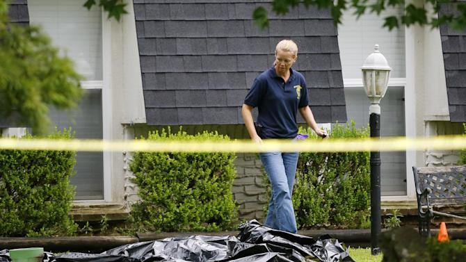 FILE - In this July 23, 2015 file photo, an investigator walks past a tarp covering a body in the front yard of a house in Broken Arrow, Okla.  The Oklahoma medical examiner's office says, Monday, July 27, 2015, all five members of a Broken Arrow family killed last week died from multiple sharp-force injuries, and police have said two knives and a small hatchet were found at the scene. (AP Photo/Sue Ogrocki, File)
