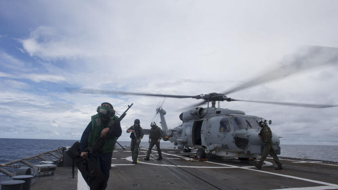 In this Oct. 15, 2012 photo, a sailor on flight deck duty, left, carries sniper rifles as sharpshooters leave the helicopter after returning from a routine patrol onboard the USS Underwood in international waters near Panama.  In October, the 30-year-old ship was patrolling the Caribbean waters off Panama, as part of a multi-national effort to hit illicit trafficking routes on both coasts of the Central American isthmus. The deployment was the Underwood's last voyage, with 10 other U.S. Navy ships scheduled to be decommissioned early next year. (AP Photo/Dario Lopez-Mills)