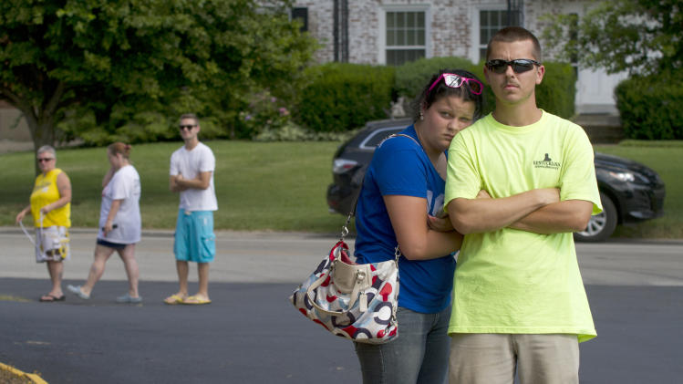 Residents Kora Thompson, left, and Joey Hopper watch activity at the scene of the Lakeview Condominiums shooting in Louisville, Ky., on Wednesday, June 19, 2013.  Three people were shot to death and a fourth was seriously injured at a condominium building Wednesday. (AP Photo/The Courier-Journal, Matt Herp) NO SALES; MAGS OUT; NO ARCHIVE; MANDATORY CREDIT