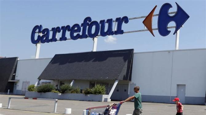 A customer pushes a shopping trolley as he leaves the Carrefour hypermarket in Brive-La-Gaillarde