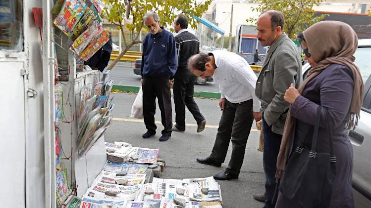 Iranians look at newspaper reports covering the landmark deal on the country's nuclear ambitions in Tehran on November 25, 2013