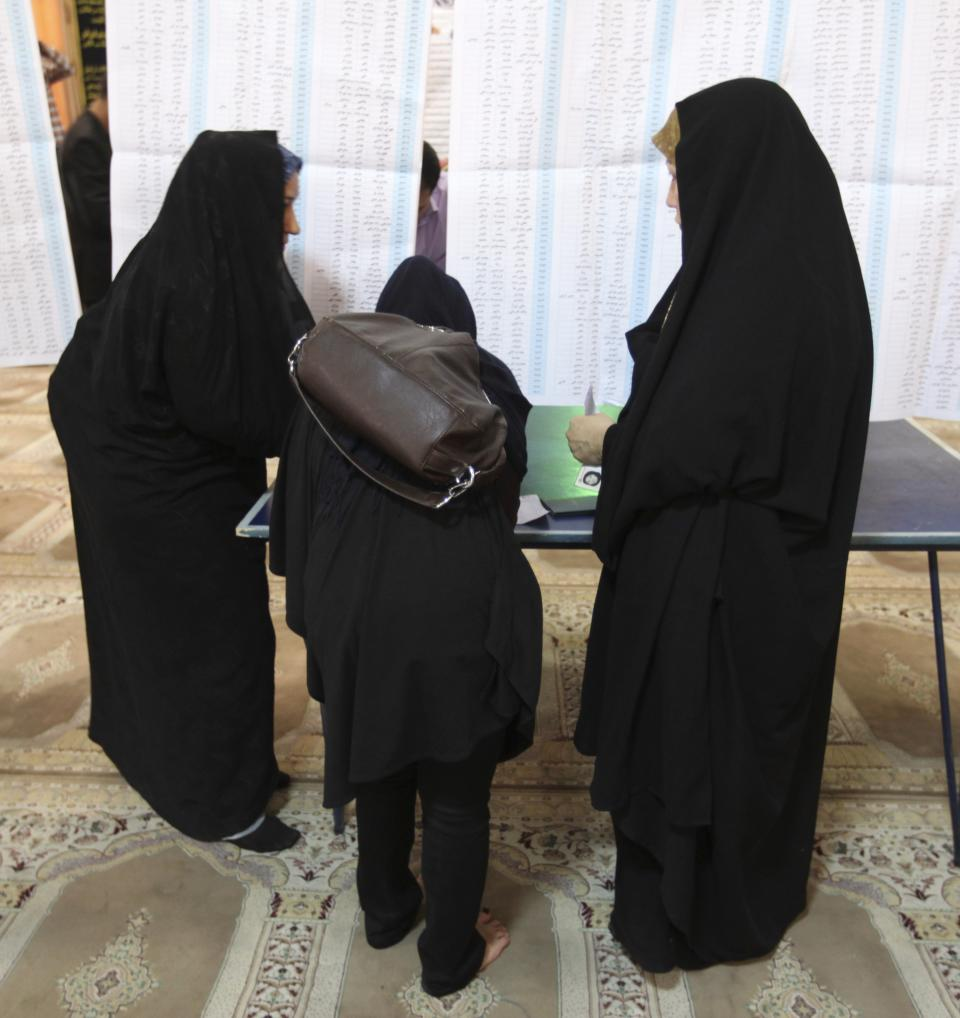 Iranian women attend a polling station to vote for the presidential and municipal councils elections in downtown Tehran, Iran, Friday, June 14, 2013. (AP Photo/Vahid Salemi)