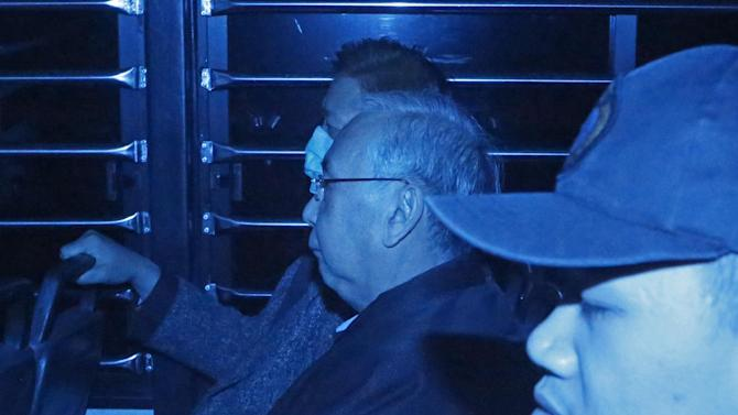 In this photo taken through a tinted glass, former Hong Kong Chief Secretary Rafael Hui, center, and former chief operating officer of the Hong Kong Futures Exchange Ltd. Francis Kwan, left, are escorted by Hong Kong Correctional Services inside a van outside the High Court in Hong Kong, Monday, Dec. 22, 2014. A Hong Kong jury found a billionaire property developer and former top government official Hui guilty of corruption after a high profile trial. Property magnate Thomas Kwok was Friday convicted of conspiracy for making HK$8.5 million (US$1.1 million) of payments to Hui. Middlemen Kwan, were found guilty of conspiracy charges. (AP Photo/Kin Cheung)