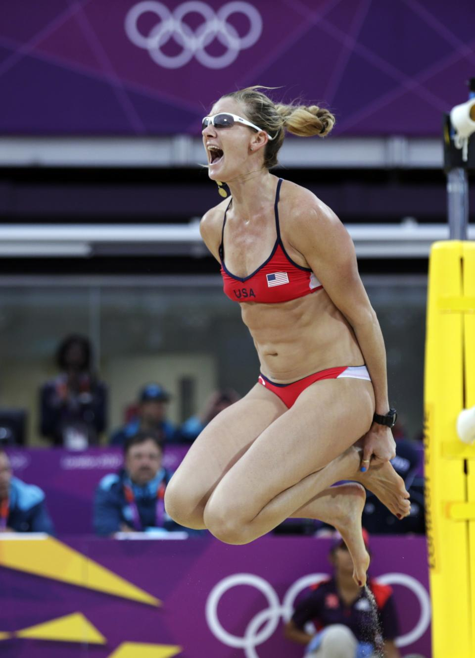 Kerri Walsh Jennings of the United States leaps in the air after beating China in two sets during a women's semi-final beach volleyball match at the 2012 Summer Olympics, Tuesday, Aug. 7, 2012, in London. (AP Photo/Dave Martin)