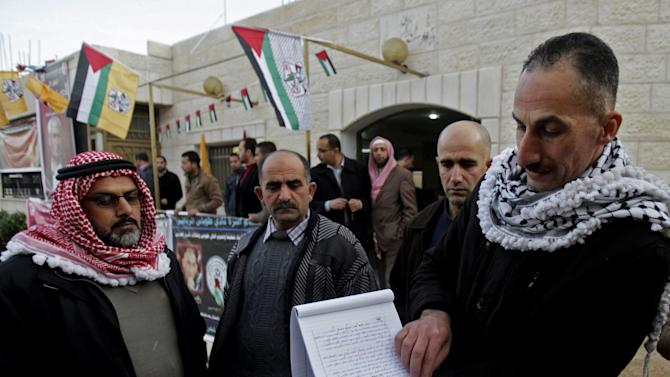 """In this Friday, Jan. 3, 2014 photo, Jamal Abu Muhsin, second right, who is among hundreds of Palestinians having spent their time in Israeli prisons pursuing an education and was recently released, shows his university degree earned at an Israeli prison in the West Bank town of Tubas near Jenin. Abu Muhsin spent his time in prison pursuing an education _ a program that has been praised by Palestinians but has caused a stir with Israelis who believe that murderers are being undeservedly coddled. """"When I found myself in jail for life, I was faced with two options: either I make meaning for my life or waste my life and my mind behind bars,"""" said Abu Muhsin, now 42, from his home in the West Bank city of Tubas. (AP Photo/Nasser Ishtayeh)"""
