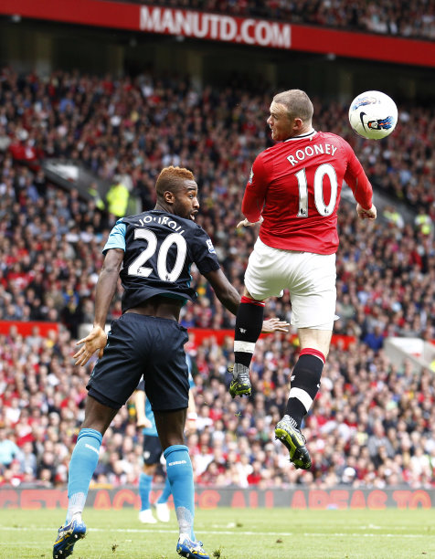 Manchester United's Wayne Rooney, right, vies for ball against Arsenal's Johan Djourou during their English Premier League soccer match at Old Trafford, Manchester, England, Sunday Aug. 28, 2011. (AP Photo/Jon Super)