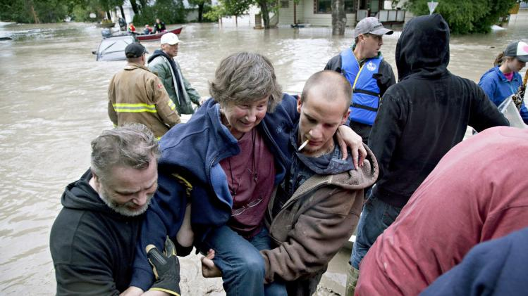A woman is rescued from the flood waters in High River, Alberta on Thursday, June 20, 2013 after the Highwood River overflowed its banks. Calgary city officials say as many as 100,000 people could be forced from their homes due to heavy flooding in western Canada, while mudslides have forced the closure of the Trans-Canada Highway around the mountain resort towns of Banff and Canmore. (AP Photo/The Canadian Press, Jordan Verlage)