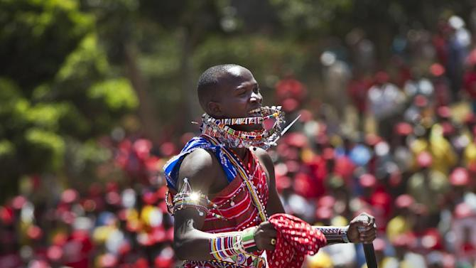 An entertainer performs a traditional Maasai jumping dance for the crowd prior to the arrival of Kenyan Presidential candidate Uhuru Kenyatta, at his campaign's final rally at Uhuru Park in Nairobi, Kenya, Saturday March 2, 2013. Kenya's top two presidential candidates - Uhuru Kenyatta and Raila Odinga - held their final rallies Saturday before large and raucous crowds ahead of Monday's vote, which is the first nationwide election since Kenya's December 2007 vote descended into tribe-on-tribe violence that killed more than 1,000 people. (AP Photo/Ben Curtis)