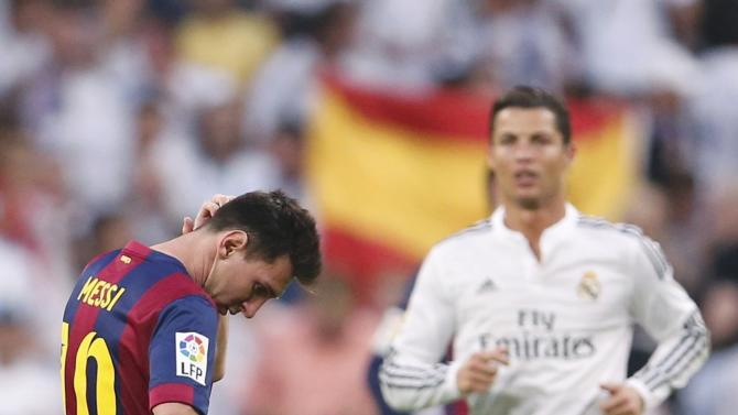 "Barcelona's Messi reacts as Real Madrid's Ronaldo closes in after Real Madrid scored a third goal during their Spanish first division ""Clasico"" soccer match at the Santiago Bernabeu stadium in Madrid"