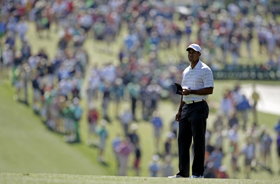 Tiger Woods checks his course notes before taking his second shot on the first fairway during the third round of the Masters golf tournament Saturday, April 7, 2012, in Augusta, Ga. (AP Photo/Chris O'Meara)