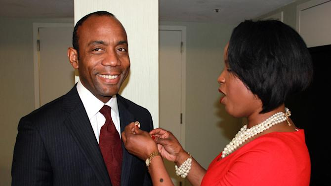 In this image provided by the NAACP, Roslyn Brock, right, chairman of the national board of directors for the NAACP, puts a NAACP pin on new national president and CEO, Cornell William Brooks on Saturday, May 17, 2014, in Ft. Lauderdale, Fla. The selection of Brooks came as the United States marked the 60th anniversary of the Brown v. Board of Education decision by the U.S. Supreme Court, which outlawed segregation in public schools. The lawsuit was argued by the organization's legal arm. (AP Photo/NAACP, J. Adams)