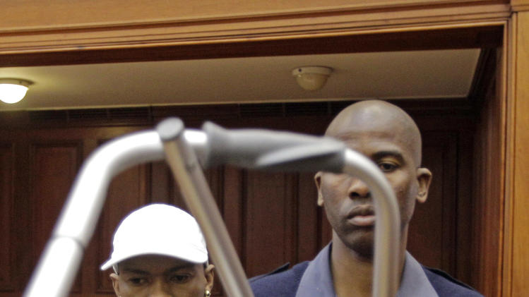 Xolile Mngeni, accused of the slaying of Anni Dewani, is escorted by a South African Policeman holding his walking frame, before the reading of his verdict, in a courtroom. in Cape Town, South Africa, Monday, Nov. 19, 2012, Mngeni,was arrested for the killing of 28-year-old Anni Dewani. Prosecutors say Mngeni was hired by Dewani's British husband to carry out the November 2010 killing, which was made to look like a car hijacking. (AP Photo/Schalk van Zuydam)