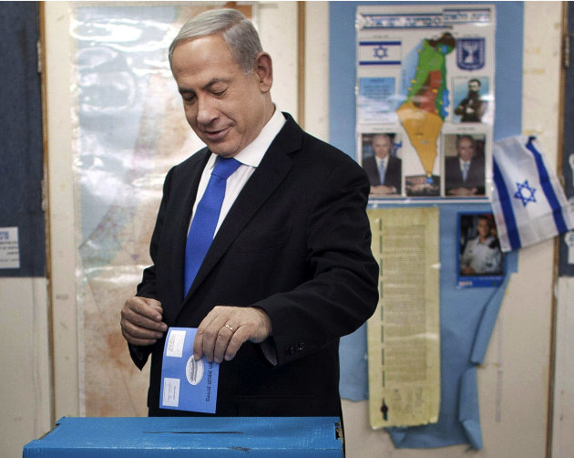 Israeli Prime Minister Benjamin Netanyahu casts his ballot together with his wife Sara, left and sons Yair and Avner, background left,  at a polling station in Jerusalem, Tuesday, Jan. 22, 2013. Israe