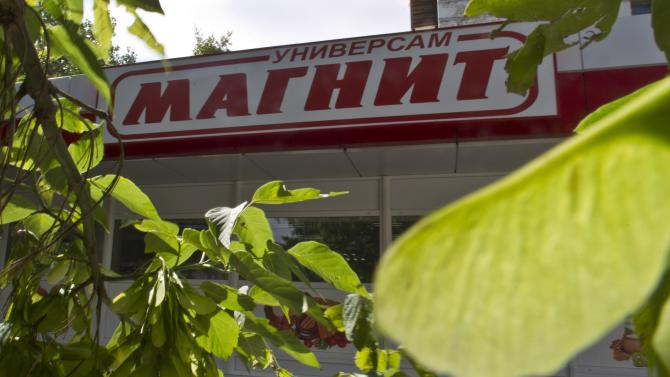 File photo of leaves framing the front of a grocery store owned by retailer Magnit in Moscow