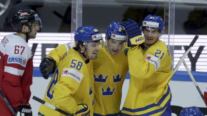 Sweden's Forsberg celebrates after scoring a goal against Austria with his teammates Lander and Eriksson during their Ice Hockey World Championship game at the O2 arena in Prague