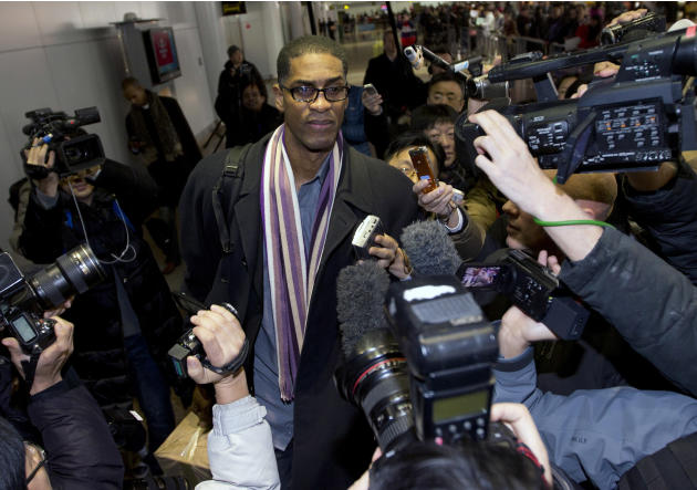 Former NBA basketball star Charles D. Smith, center, is mobbed by journalists upon arrival at the Beijing Capital International Airport in Beijing from Pyongyang, North Korea, Friday, Jan. 10, 2014. A