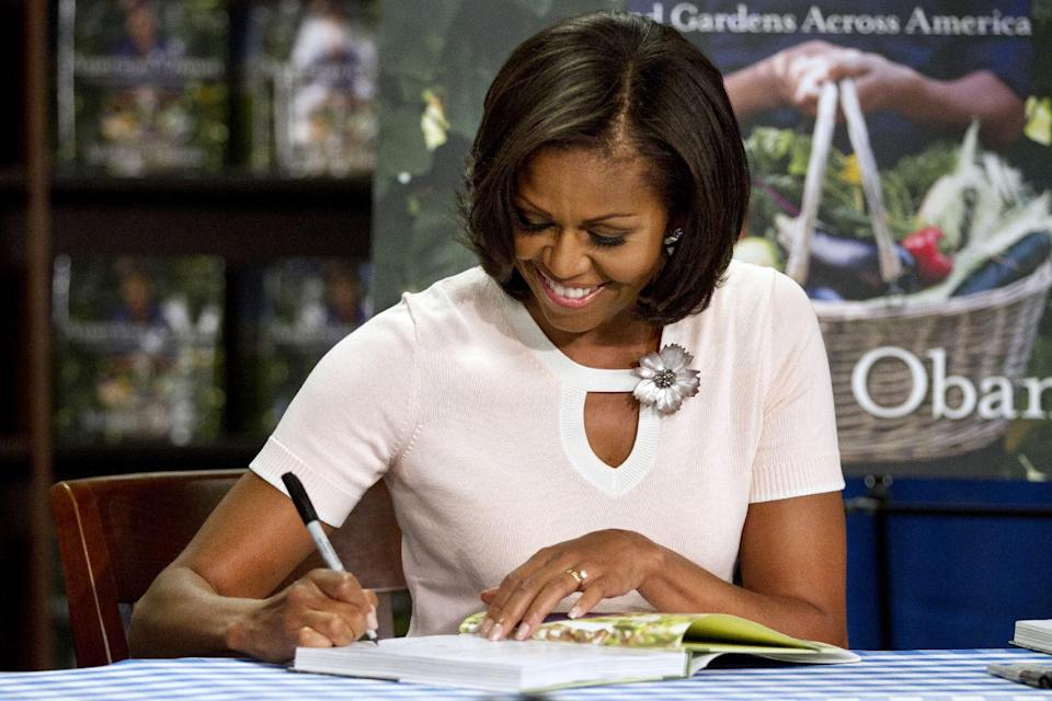 "First lady Michelle Obama signs a copy of her book, ""American Grown: The Story of the White House Kitchen Garden and Garden Across America,"" in Washington, Tuesday, June 12, 2012.  (AP Photo/Jacquelyn Martin)"