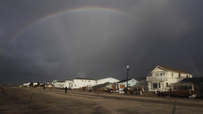 A rainbow forms over Breezy Point in the New York City borough of Queens, in the aftermath of superstorm Sandy, Tuesday, Oct. 30, 2012, in New York. The fire destroyed between 80 and 100 houses Monday night in the flooded neighborhood. (AP Photo/Frank Franklin II)