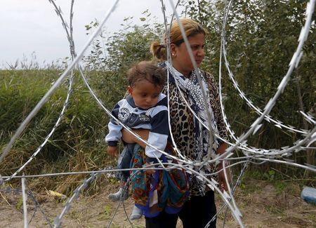 A Syrian migrant carries a child while standing behind a fence before crossing the Hungarian-Serbian border near Asotthalom