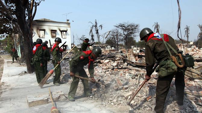 Myanmar soldiers clean debris from destroyed buildings following ethnic unrest between Buddhists and Muslims in Meikhtila, Mandalay division, about 550 kilometers (340 miles) north of Yangon, Myanmar, Sunday, March 24, 2013. Myanmar's army took control of a ruined central city on Saturday, regaining control after several days of clashes between Buddhists and Muslims that killed dozens of people and left scores of buildings in flames in the worst sectarian bloodshed to hit the Southeast Asian nation this year.(AP Photo/Khin Maung Win)