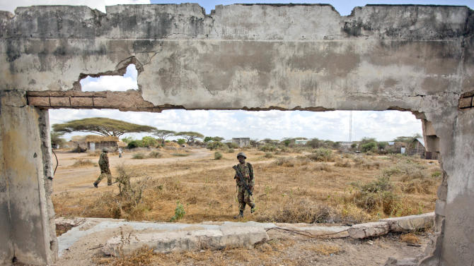 Seen through the ruins of a building damaged during a previous conflict, Kenyan army soldiers patrol in Tabda, inside Somalia, Monday, Feb. 20, 2012. Kenya's military crossed the border into Somalia in an offensive against Somali militant group al-Shabab in October after Somali gunmen carried out several kidnappings in Kenya, and al-Qaida leader Ayman al-Zawahri announced a merger between al-Shabab with al-Qaida in early February. (AP Photo/Ben Curtis)