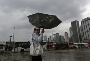 A woman braves strong wind near the waterfront in Hong…
