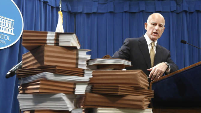FILE - In this Jan. 8, 2013 file photo, Gov. Jerry Brown gestures to a stack of reports on California prisons as he discusses his call for federal judges to return control of California prisons to the state during a news conference at the Capitol in Sacramento, Calif. Brown is criticizing attorneys representing inmates and court-appointed masters and experts who he says have a financial incentive to drag out lawsuits against the state. (AP Photo/Rich Pedroncelli, File)