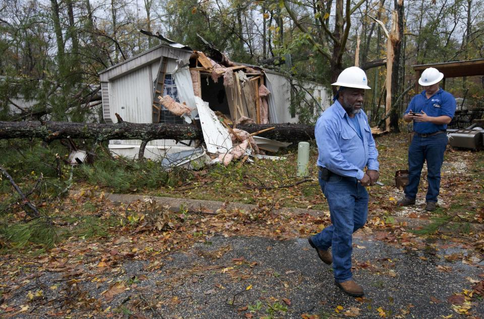 Gas company employees go from house to house turning off the gas after a wind storm damaged this trailer park in Auburn, Ala., Wednesday, Nov. 16, 2011.  A path of storms swept across the state leaving behind fallen trees and some heavy wind damage.  (AP Photo/Dave Martin)