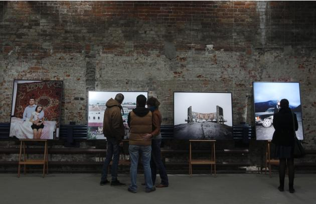 "People visit the photo exhibition entitled ""The Sochi Project"" by Dutch photographer Hornstra and his colleague van Bruggen at Photodoc centre in Moscow"