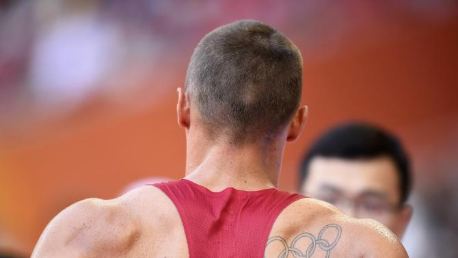 A tattoo of Olympic rings is seen on the back of Trey Hardee of the U.S. as he walks out of the field after getting injured in the long jump event of the men's decathlon during the 15th IAAF World Championships at the National Stadium in Beijing