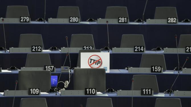 """A poster which reads """"no TTIP"""" is seen on the desk of a member of the European Parliament during a debate in Strasbourg"""