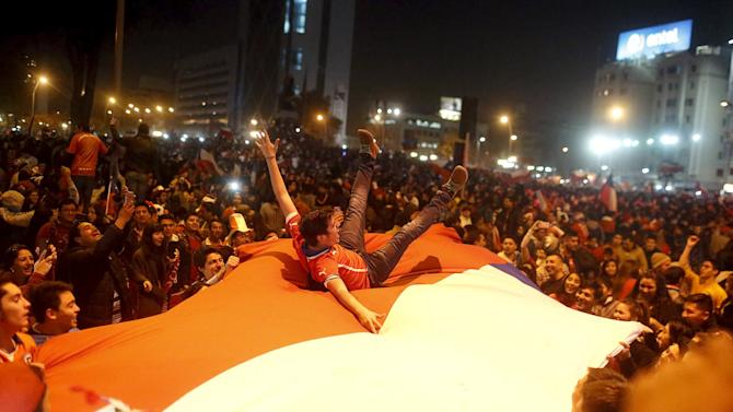 Fan jumps on a giant Chilean national flag during celebrations on the street following Chile's victory over Argentina in their Copa America final soccer match in Santiago, Chile