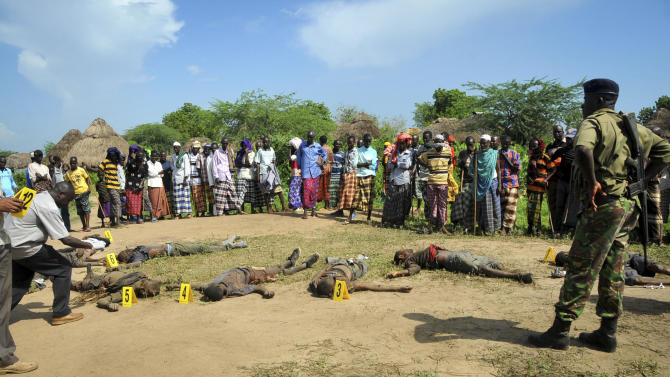 Villagers and police view the bodies of suspected attackers from the Pokomo tribe, following tribal clashes in Kipao village in the Tana River Delta region of southeastern Kenya Friday, Dec. 21, 2012. At least 39 people including men, women, children, and attackers, were killed when farmers from the Pokomo tribe, armed with spears and AK-47 rifles, raided a village of semi-nomadic Orma herders early Friday in renewed fighting between two communities with a history of violent animosity, a police official said. (AP Photo)