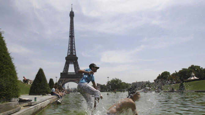 FILE - In this June 27, 2011 file photo, Parisians leap into the Trocadero fountain to cool off in Paris. Heat rising up from cities such as New York, Paris and Tokyo might be remotely warming up winters far away in some rural parts of Alaska, Canada, and Siberia. At least that's what a surprising study suggests. (AP Photo/Michel Euler, File)