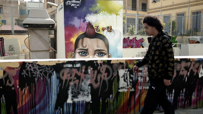 A man walks past graffiti in capital Nicosia, on Friday, March 29, 2013.  Banks in Cyprus are open for normal business for the second day, but with strict restrictions on how much money their clients can access, after being shut for nearly two weeks.(AP Photo/Petros Giannakouris)