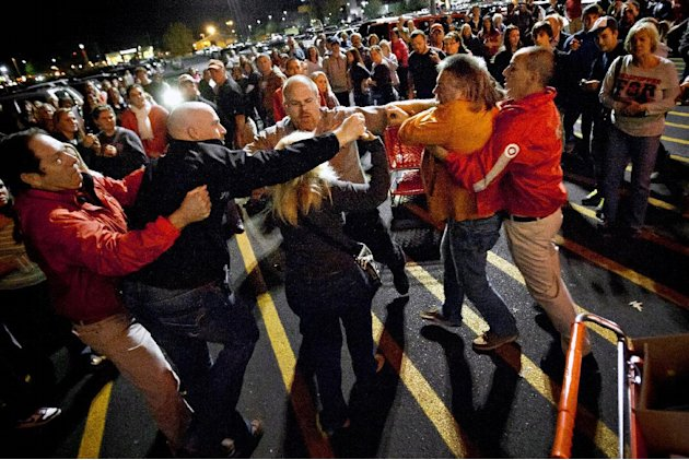 A crowd gathers as security guards break up a fight between shoppers waiting in line just as the doors open for Black Friday shopping at Target, Thursday, Nov. 22, 2012, in Bowling Green, Ky. Despite
