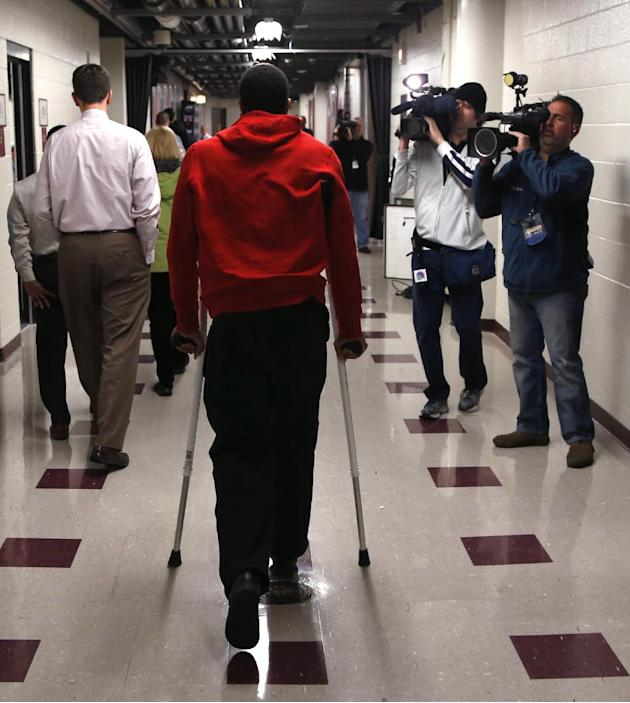 Chicago Bulls' Derrick Rose walks down a hall on crutches after an NBA basketball news conference about his injured knee at the United Center Thursday, Dec. 5, 2013, in Chicago