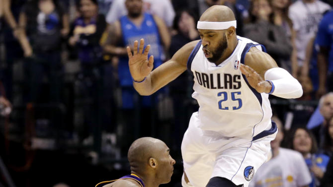 Dallas Mavericks' Vince Carter (25) leaps at Los Angeles Lakers' Kobe Bryant, left, in the second half of an NBA basketball game, Sunday, Feb. 24, 2013, in Dallas. Bryant scored 38 points in their 103-99 win. (AP Photo/Tony Gutierrez)