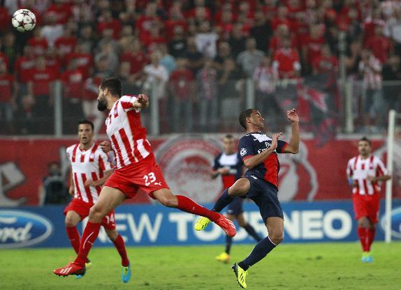 Olympiakos' Dimitris Siovas, left and  PSG's Lucas fight for the ball  during the soccer Champions League group C match between Olympiakos and Paris Saint Germain in Piraeus, Greece, Tuesday, Sept. 17
