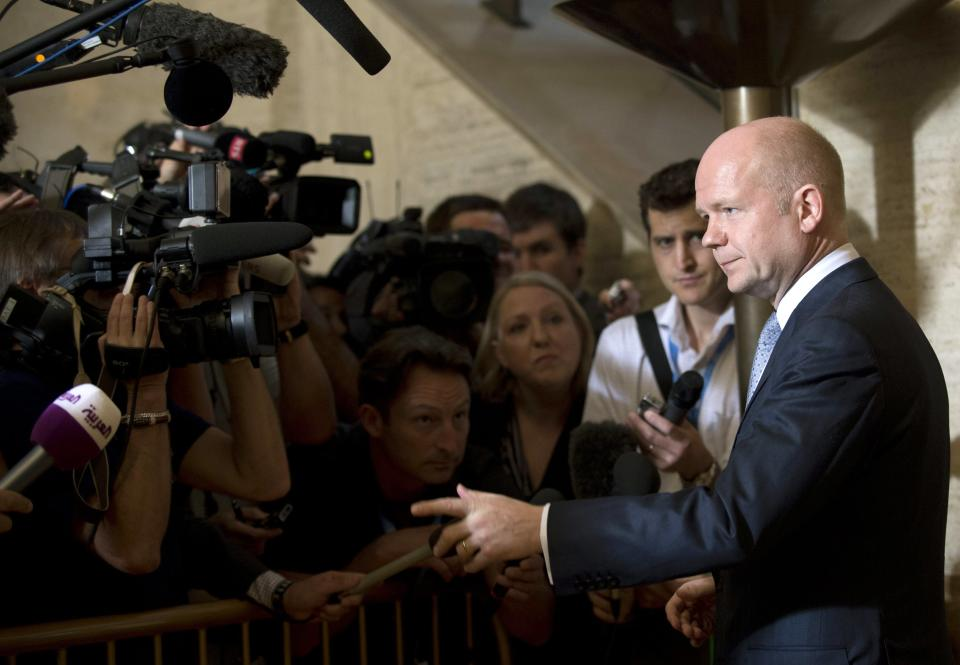 British Foreign Minister William Hague, right, talks to media representatives upon his arrival for a meeting of the Action Group for Syria at the European headquarters of the United Nations,  in Geneva, Switzerland, Saturday, June 30, 2012. (AP Photo/Keystone, Martial Trezzini)