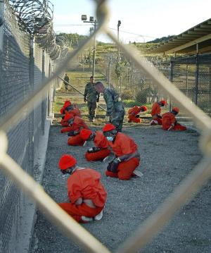 FILE - In this Jan. 11, 2002 file photo, released by the U.S. Department of Defense, detainees wearing orange jump suits sit in a holding area as military police patrol during in-processing at the temporary detention facility Camp X-Ray on Guantanamo Bay U.S. Naval Base in Cuba. Open for 10 years on Wednesday Jan. 11, 2012, the Guantanamo Bay prison seems more established than ever. The deadline set by President Barack Obama to close it came and went two years ago. No detainee has left in a year because of restrictions on transfers, and indefinite military detention is now enshrined in U.S. law. Prisoners at the U.S. base in Cuba plan to mark the day with sit-ins, banners and a refusal of meals, said Ramzi Kassem, a lawyer who represents seven inmates. (AP Photo/U.S. Navy, Shane T.McCoy, File)