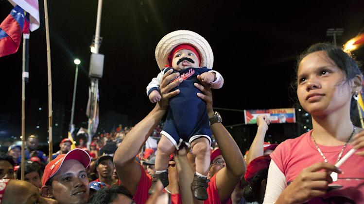 Supporters hold a toddler wearing a Maduro-style mustache at the closing campaign rally for Venezuela's acting President Nicolas Maduro in Caracas, Venezuela, Thursday April 11, 2013. Maduro, the hand-picked successor of Venezuela's late President Hugo Chavez, is running for president against opposition candidate Henrique Capriles on April 14.  (AP Photo/Ramon Espinosa)