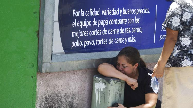 A woman mourns near the body of a man, an alleged thief killed during an assault on a public bus at Zona 10 in Guatemala City